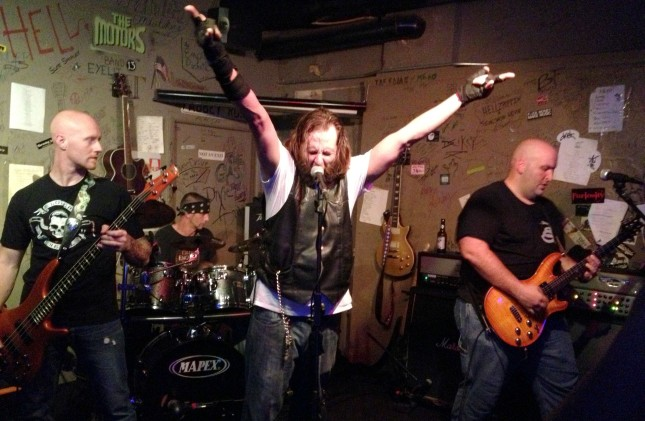 Lead singer Ralph Dunn throws up his hands during The Devil and the Southern Fellowship's set at Cafe Acoustic in St. Joseph, Missouri on 9/13/13. Left to right; Sean Selecman on bass, Danny Gray on drums, Ralph Dunn at the mic and Chad O'Callaghan on lead guitar; guitarist Sean Sollars is out of frame to stage left.