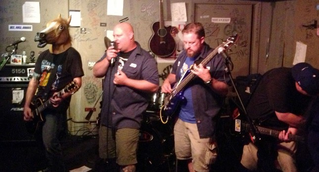 IT brings cinema to the small stage at Cafe Acoustic in St. Joseph, Missouri on 9/13/13. Left to right: Todd Cooper wearing a horse head and playing guitar, Rick Hoffman on vocals, Will Stuck on bass and Ric Howard on guitar; obscured from view is drummer Dan Thompson.